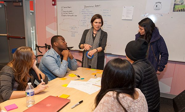 students sitting at table discussing project with professor