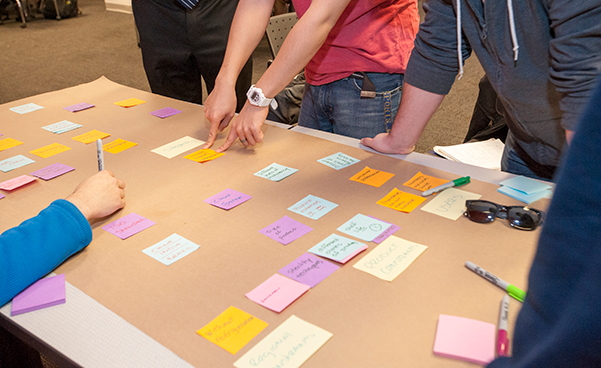 students discussing sticky notes on project board