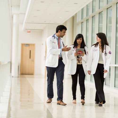 health sciences students having a discussion walking down a hallway